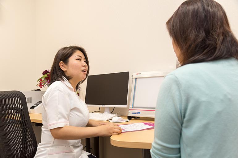 個室の診察室での診断を受ける女性